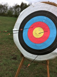 Archery target with arrows around the edge